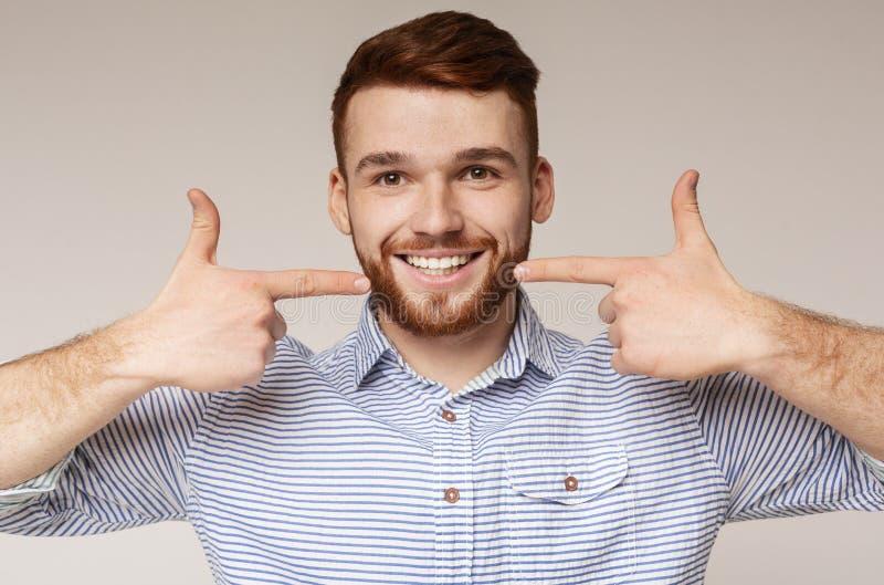 Jeune homme millénaire montrant son beau sourire photos stock