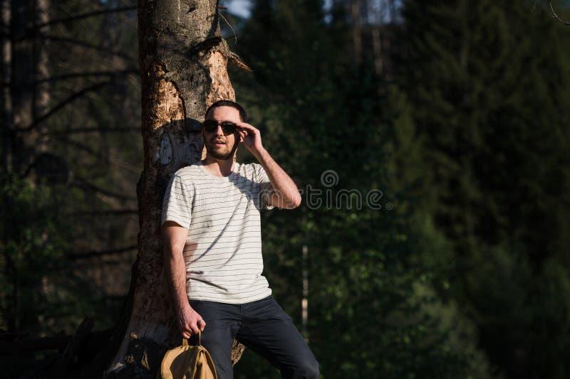 Jeune homme modèle barbu attirant bel avec le sac à dos dans les bois posant près de l'arbre images stock