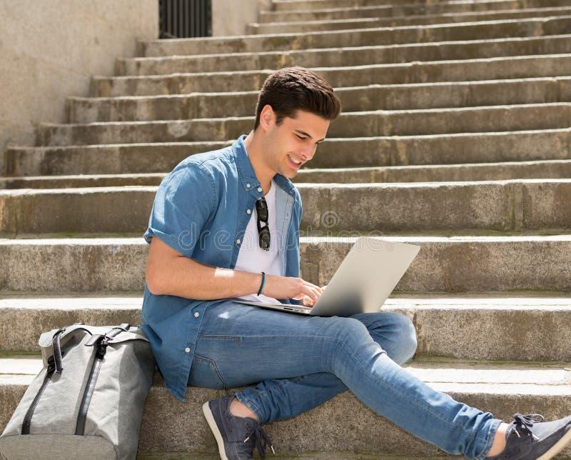 Jeune homme moderne attirant travaillant avec l'ordinateur dans la ville dessus photos libres de droits