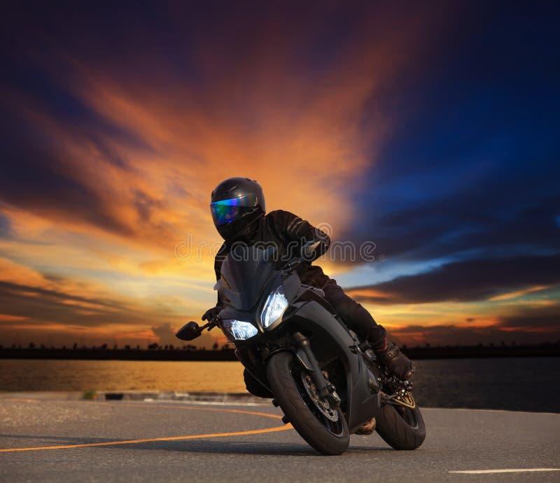 Jeune homme montant la courbe de penchement de grande moto de vélo sur l'asphalte salut image stock