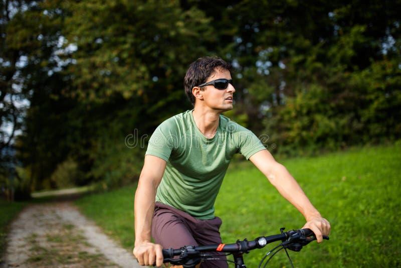Jeune homme montant son vélo de montagne dehors images stock