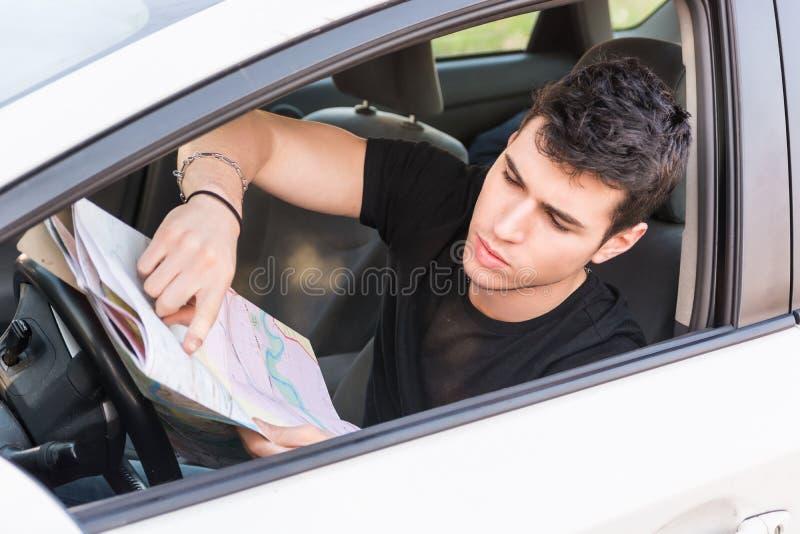 Jeune homme montrant la carte à l'intérieur d'une voiture photographie stock libre de droits