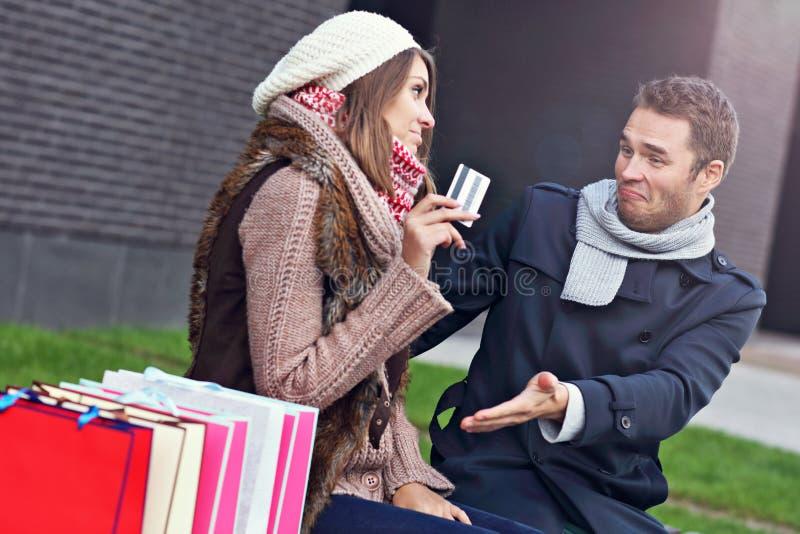 Jeune homme montrant la désapprobation à la femme avec beaucoup de paniers photo stock