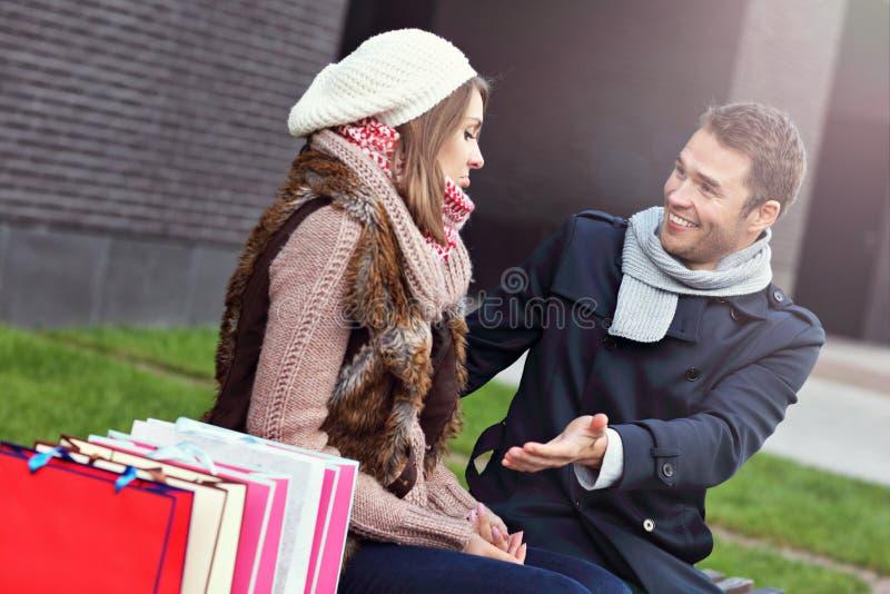 Jeune homme montrant la désapprobation à la femme avec beaucoup de paniers image stock