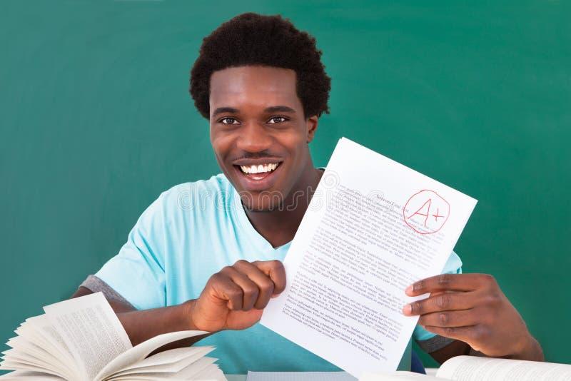 Jeune homme montrant un papier avec la catégorie A plus image libre de droits