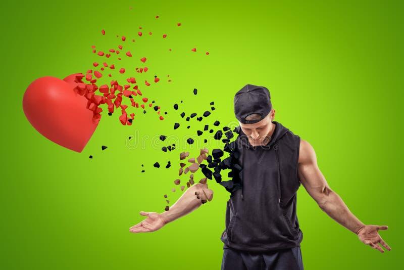 Jeune homme musculaire à l'habillement noir de sport et au coeur rouge se brisant dans de petits morceaux sur le fond vert illustration stock
