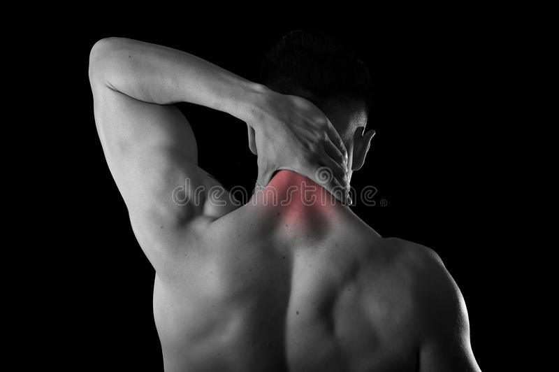 Jeune homme musculaire arrière de sport tenant le cou endolori touchant massant le secteur cervical photo stock