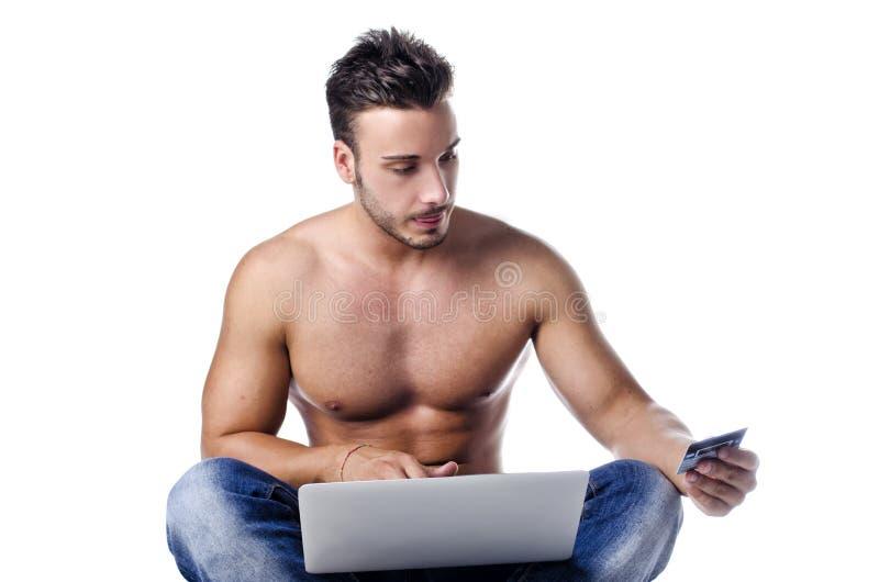Jeune homme musculaire avec l'ordinateur portable et la carte de crédit photo libre de droits