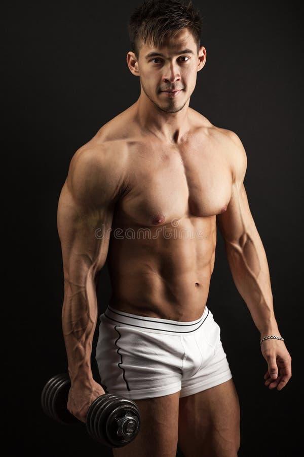 Jeune homme musculaire avec une haltère image stock