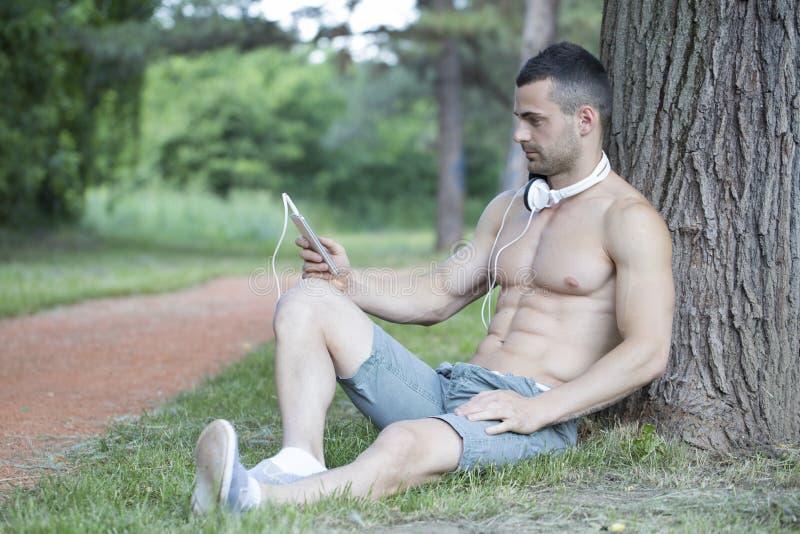 Jeune homme musculaire beau et attirant se reposant en parc et photos libres de droits