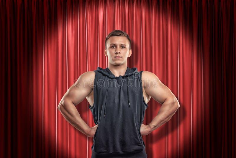 Jeune homme musculaire dans des vêtements noirs de sport sur le fond rouge de rideaux en étape images stock