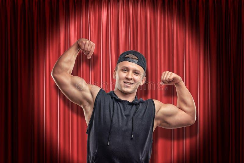 Jeune homme musculaire dans l'habillement noir de sport souriant et montrant le biceps sur le fond rouge de rideaux en étape photo libre de droits