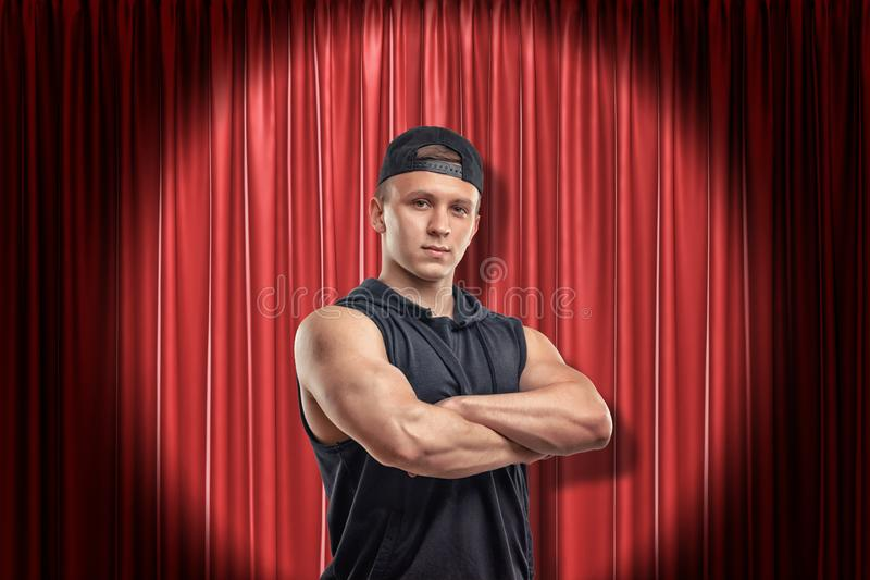 Jeune homme musculaire dans l'habillement noir de sport sur le fond rouge de rideaux en étape photo libre de droits