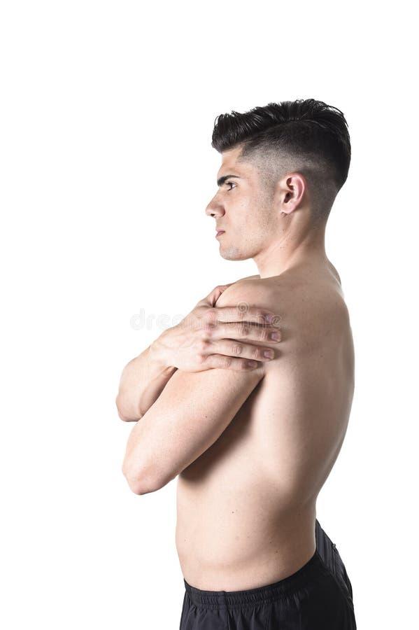Jeune homme musculaire de sport tenant l'épaule endolorie en douleur touchant le massage dans l'effort de séance d'entraînement image libre de droits