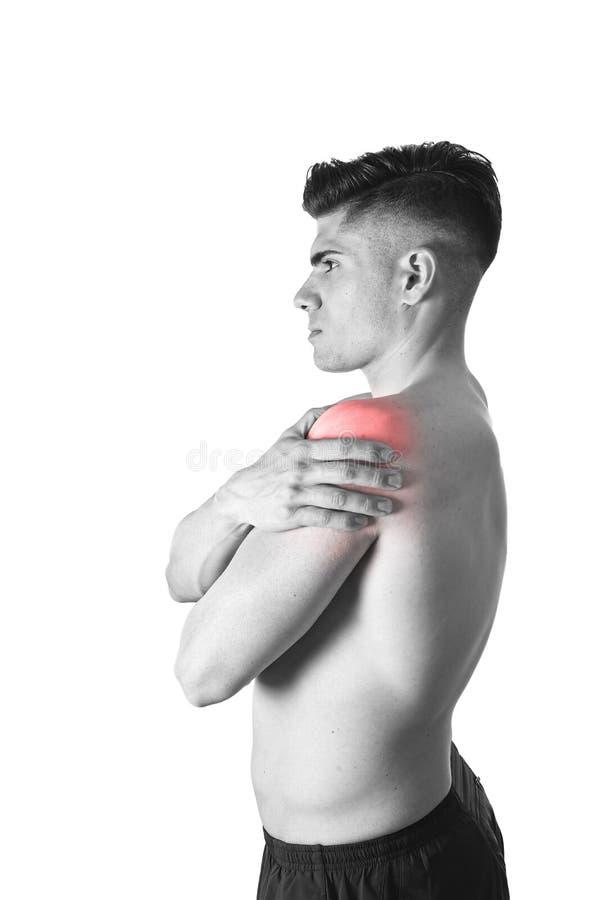 Jeune homme musculaire de sport tenant l'épaule endolorie en douleur touchant le massage dans l'effort de séance d'entraînement photographie stock libre de droits