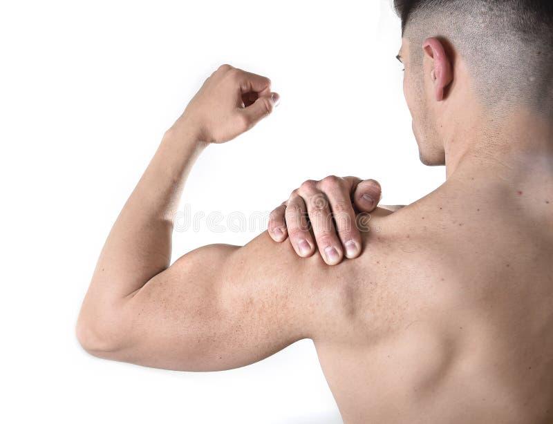 Jeune homme musculaire de sport tenant l'épaule endolorie en douleur touchant le massage dans l'effort de séance d'entraînement photo stock