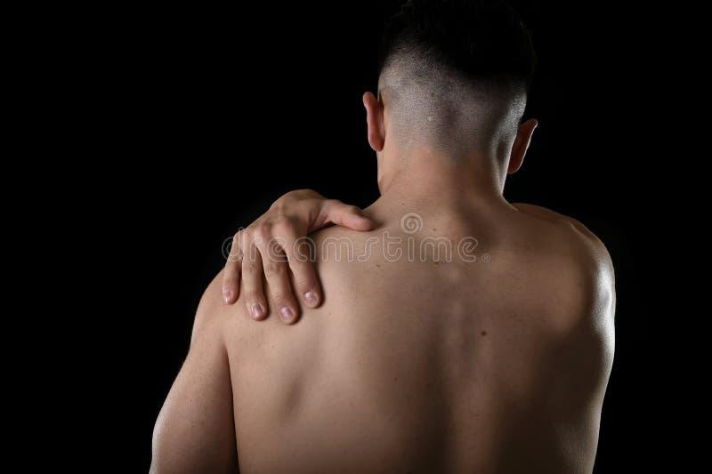 Jeune homme musculaire de sport tenant l'épaule endolorie en douleur touchant le massage dans l'effort de séance d'entraînement photos stock