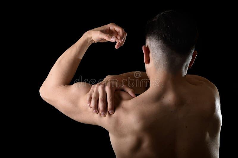 Jeune homme musculaire de sport tenant l'épaule endolorie en douleur touchant le massage dans l'effort de séance d'entraînement images libres de droits