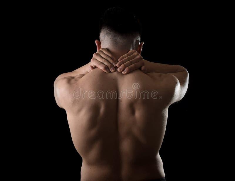 Jeune homme musculaire de sport tenant le cou endolori massant la douleur de corps de souffrance de secteur cervical images libres de droits