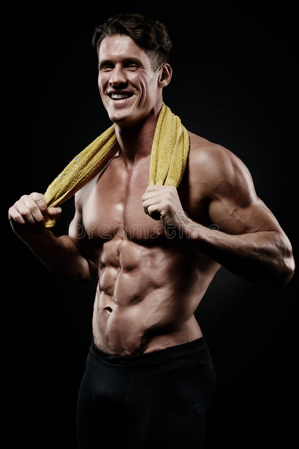 Jeune homme musculaire en bonne santé après une séance d'entraînement sur le fond foncé Fi photo stock