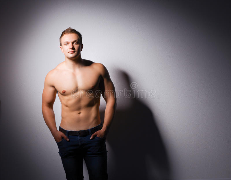 Jeune homme musculaire en bonne santé D'isolement sur le fond noir photo stock