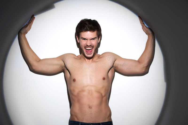 Jeune homme musculaire en bonne santé dans le projecteur photo libre de droits