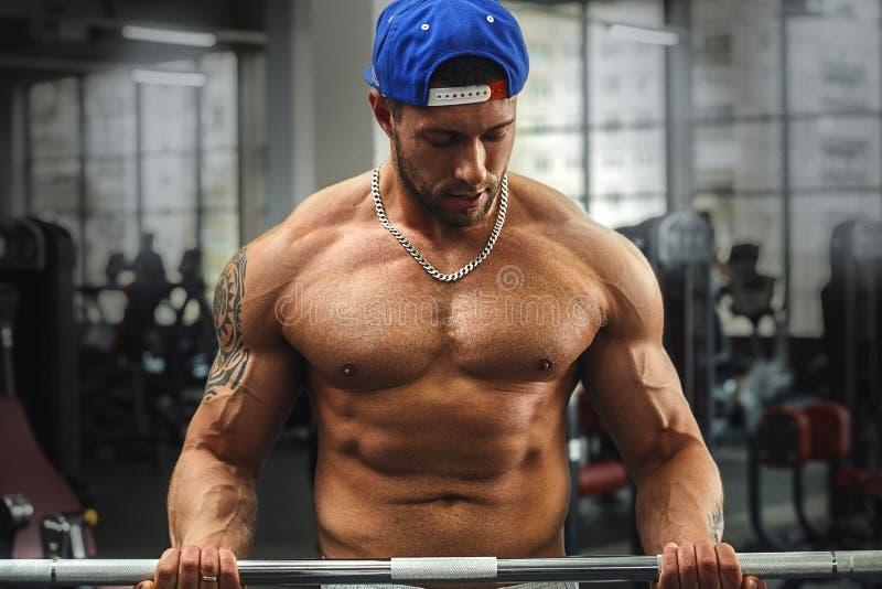 Jeune homme musculaire faisant l'exercice avec le barbell image libre de droits