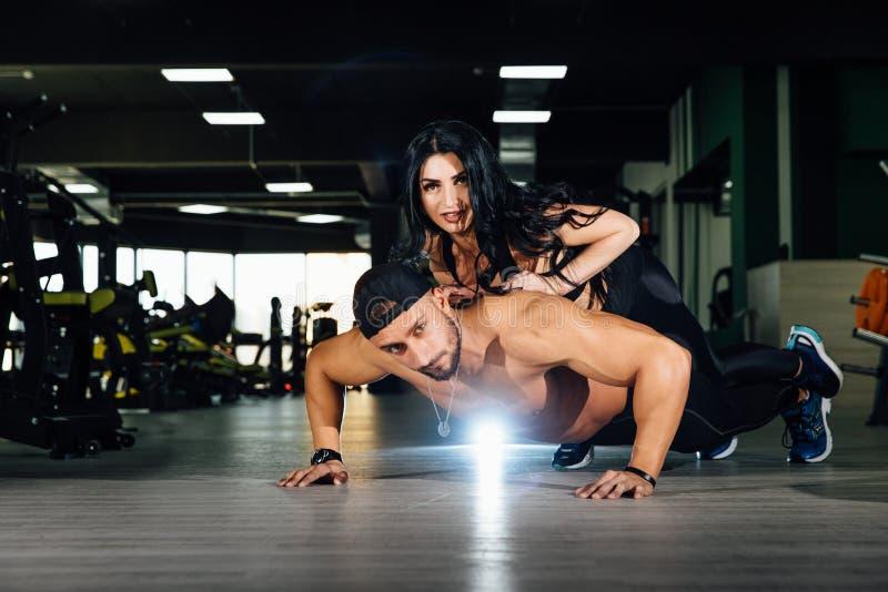 Jeune homme musculaire faisant l'exercice de pompe tandis que la fille se trouve dessus Couples de forme physique au gymnase image libre de droits