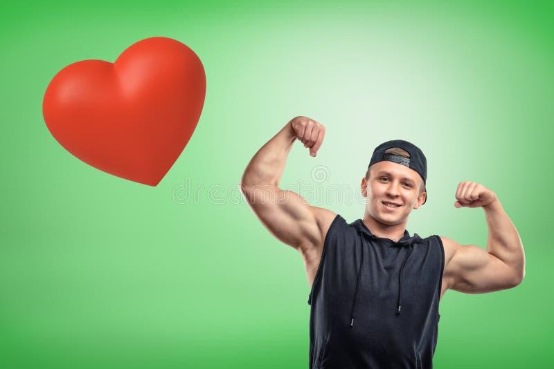Jeune homme musculaire fort montrant le biceps avec le grand coeur rouge sur le fond vert illustration de vecteur