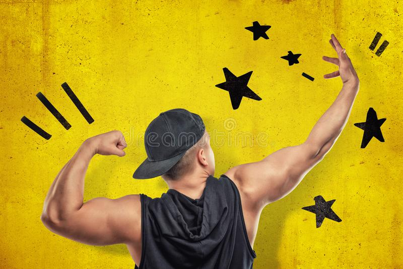 Jeune homme musculaire fort montrant le biceps avec les étoiles noires dessinées sur le fond jaune de mur images stock