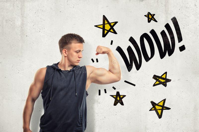 Jeune homme musculaire fort montrant le biceps avec le signe de wow et les étoiles de jaunes dessinées sur le fond blanc de mur illustration de vecteur
