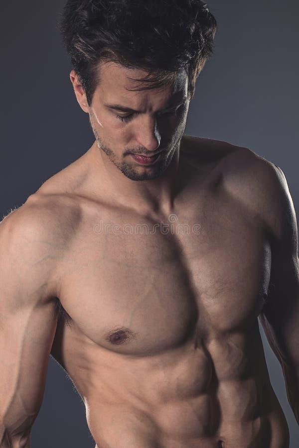 Jeune homme musculaire sans chemise beau sur le fond foncé photo stock