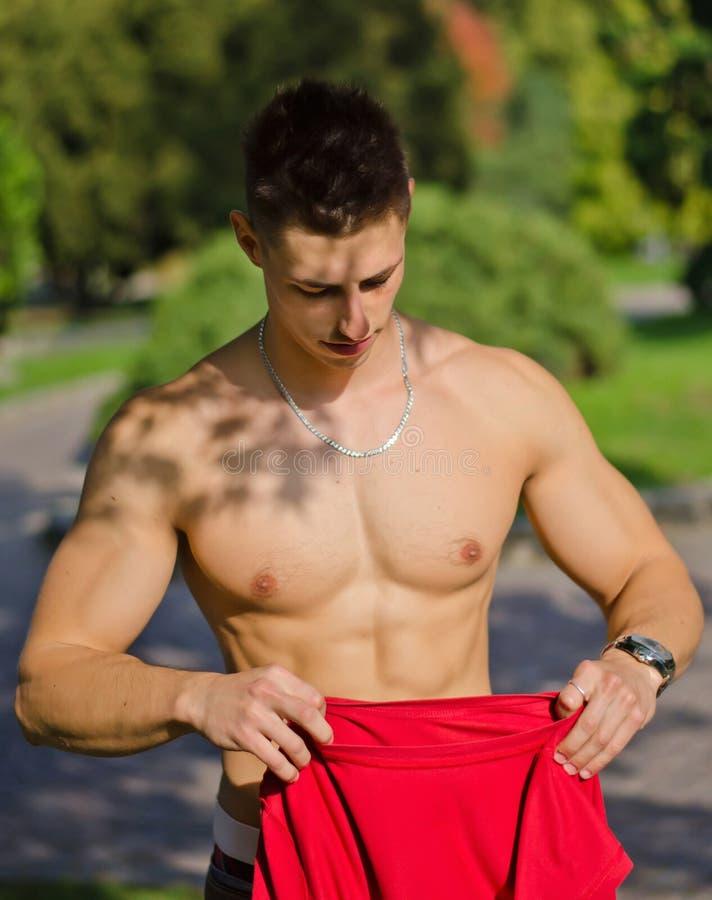 Jeune homme musculaire se déshabillant en stationnement images stock