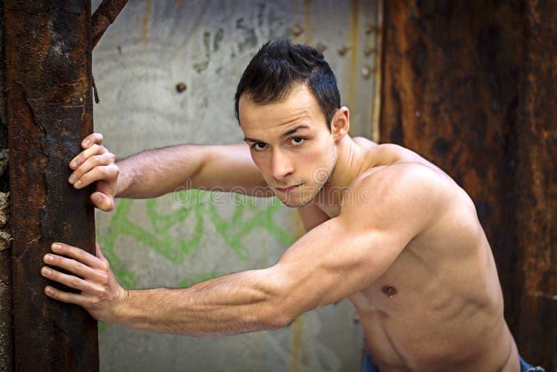 Jeune homme musculaire se penchant contre le métal rouillé images libres de droits