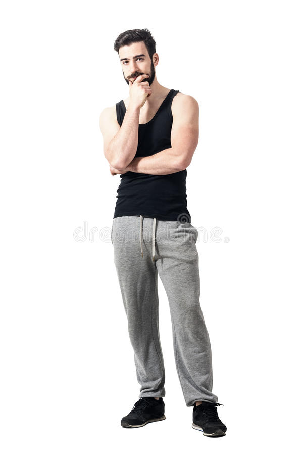 Jeune homme musculaire utilisant le tricot noir avec la main sur le menton image stock