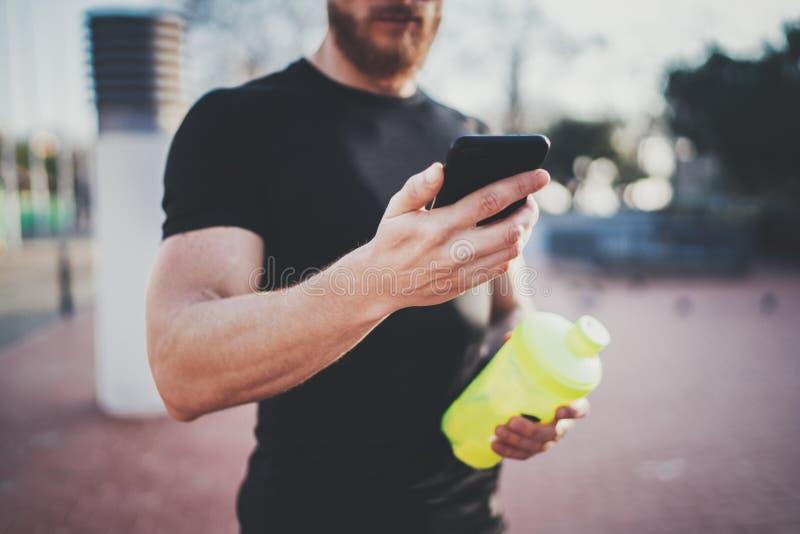 Jeune homme musculaire vérifiant des calories brûlées sur l'application de smartphone après session extérieure de bonne séance d' photographie stock