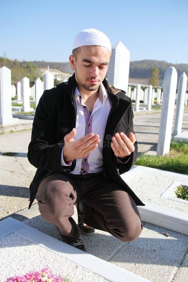 Jeune homme musulman près de la sa tombe de père photos libres de droits