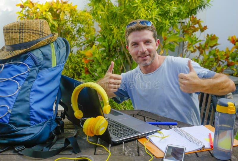 Jeune homme numérique attirant et heureux de nomade travaillant dehors avec l'extérieur courant gai et sûr d'ordinateur portable  image libre de droits