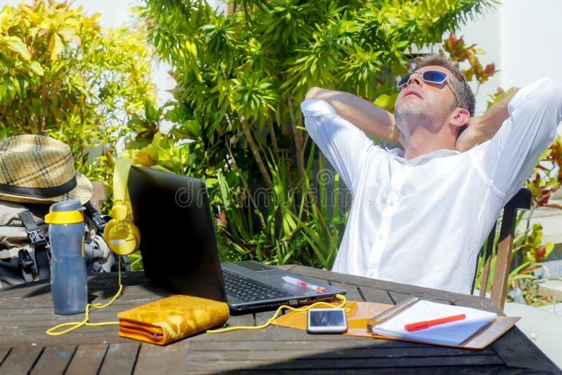 Jeune homme numérique attirant et heureux de nomade travaillant dehors du café avec l'ordinateur portable se penchant de retour d photos libres de droits