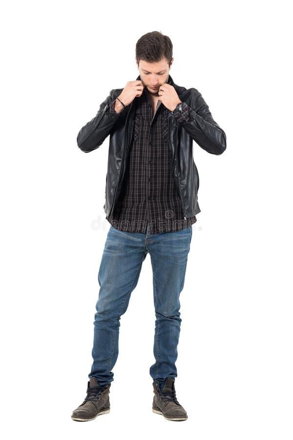 Jeune homme obtenant dessus mise la veste en cuir habillée regardant vers le bas image libre de droits