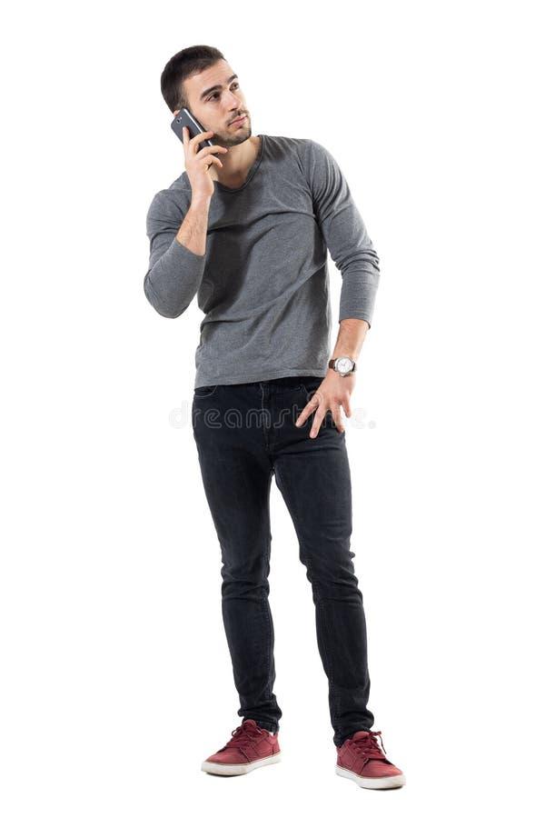 Jeune homme occasionnel à la mode parlant au téléphone portable recherchant photos stock