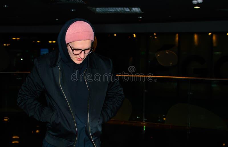 Jeune homme occasionnel à la mode se tenant sur le fond abstrait foncé et observant vers le bas image libre de droits