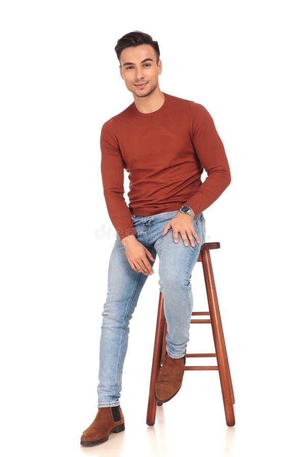 Jeune homme occasionnel assis avec la main sur la cuisse photos stock
