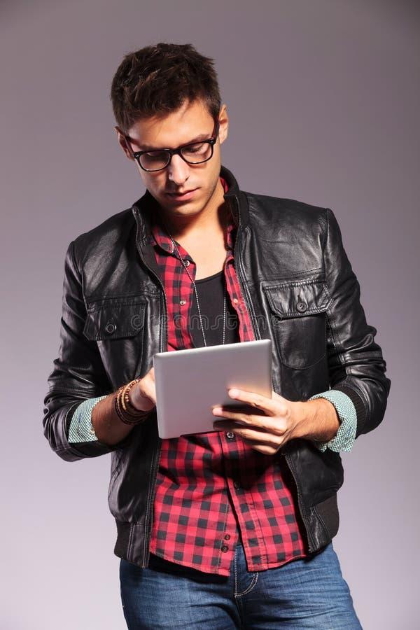 Jeune homme occasionnel avec le fonctionnement en verre sur la tablette images libres de droits