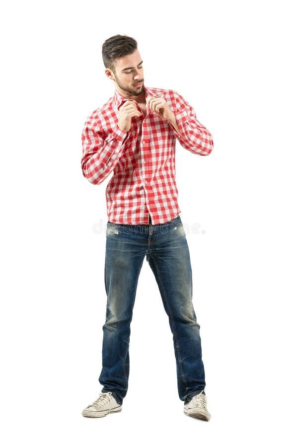 Jeune homme occasionnel boutonnant la chemise de plaid images stock