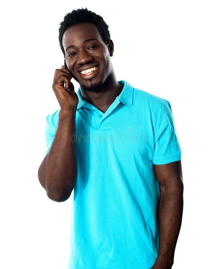 Jeune homme occasionnel communiquant au téléphone photographie stock libre de droits