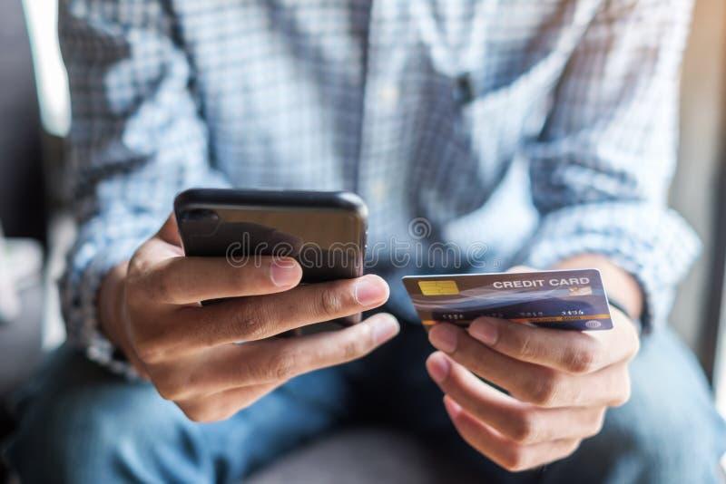 Jeune homme occasionnel d'affaires tenant la carte de crédit et à l'aide du smartphone d'écran tactile pour des achats en ligne t photo stock