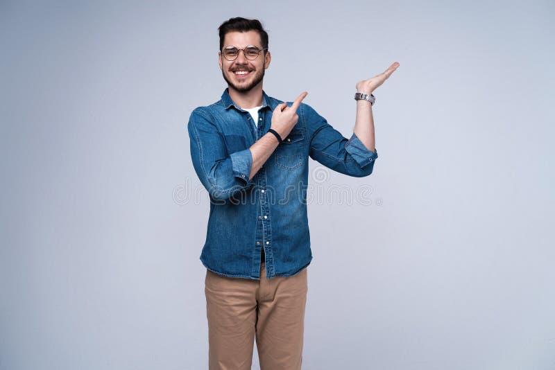 Jeune homme occasionnel de sourire présent quelque chose sur le fond gris image stock