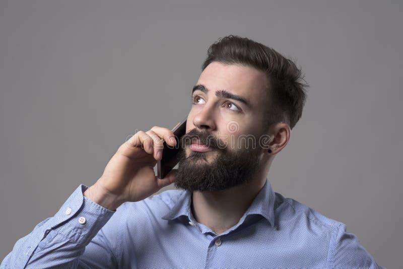 Jeune homme occasionnel futé moderne barbu d'affaires parlant au téléphone regardant le copyspace image stock