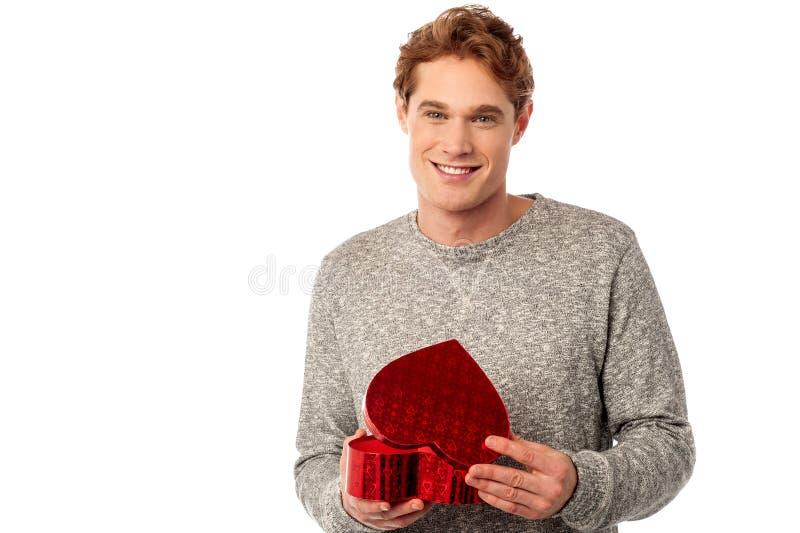 Jeune homme occasionnel ouvrant son cadeau de valentine images stock
